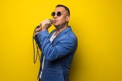 Portrai van de rijpe middendieleeftijdsmens in kostuum het zingen over de microfoon op gele achtergrond wordt geïsoleerd Zangerco royalty-vrije stock foto's