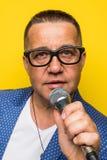 Portrai van de rijpe middendieleeftijdsmens in kostuum het zingen over de microfoon op gele achtergrond wordt geïsoleerd Zangerco stock fotografie