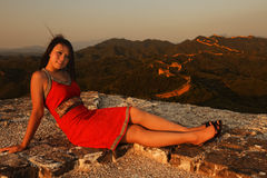 Portrail of a girl. A Chinese girl is pleased sitting on Great Wall in sunset light Royalty Free Stock Photo