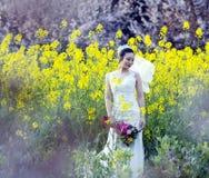 Portraint невесты с белым платьем свадьбы в поле цветка Коул Стоковые Изображения RF
