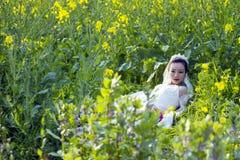 Portraint невесты с белым платьем свадьбы в поле цветка Коул Стоковое фото RF