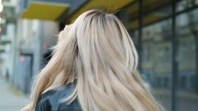 Portrair του ελκυστικού περιπάτου κοριτσιών χαμόγελου hipster κάτω από την οδό, των στροφών στη κάμερα και των χαμόγελων Υπαίθριο απόθεμα βίντεο
