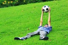 Portrair азиатского мальчика кладет вниз на траву и держит футбол Стоковая Фотография RF