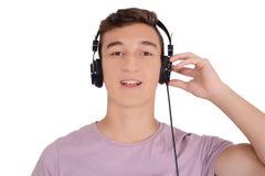 Portrair de la música que escucha adolescente sonriente con los auriculares Fotografía de archivo libre de regalías