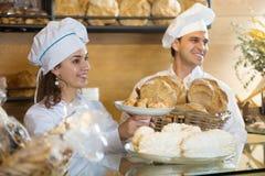 Portrair de los pasteles sonrientes del cocinero dos en panadería italiana foto de archivo libre de regalías