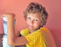 Portrair di un ragazzo felice che produce frappè per se stesso che si siede a Immagini Stock