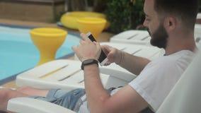 Portrair du blogger masculin de voyage, qui fait un courrier dans les réseaux sociaux sur son smartphone banque de vidéos