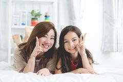 Portrair of Young mother with her daughter rest on bed. Royalty Free Stock Image