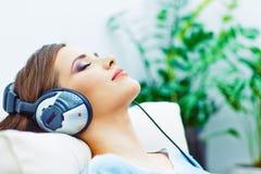 Portrait à la maison de jeune femme Fille de sommeil avec des écouteurs Image stock