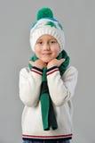 Portrait à la mode d'un garçon adorable d'enfant en bas âge dans le chapeau et l'écharpe chauds d'hiver sur le fond gris Photographie stock