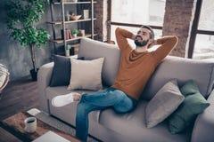 Portrait à lui il gentil type satisfait gai gai barbu attirant s'asseyant sur le divan ayant le repos au grenier industriel photographie stock libre de droits