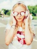 Portrait élégant de mode d'été de la fille blonde assez sexy de jeunes posant dans des lunettes de soleil, T-shirt, et écoutant l Photos stock