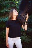 Portrait émotif d'une femelle dans l'amour avec des chevaux, animal familier frison noir de pur sang d'étalon Images libres de droits