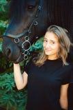 Portrait émotif d'une femelle dans l'amour avec des chevaux, animal familier frison noir de pur sang d'étalon Photo stock