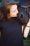 Portrait émotif d'une femelle dans l'amour avec des chevaux, animal familier frison noir de pur sang d'étalon Photos stock
