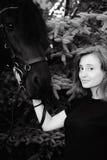 Portrait émotif d'une femelle dans l'amour avec des chevaux, animal familier frison noir de pur sang d'étalon Image libre de droits