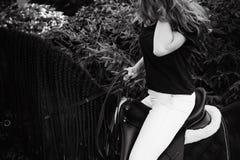 Portrait émotif d'une femelle dans l'amour avec des chevaux, animal familier frison noir de pur sang d'étalon Photographie stock libre de droits