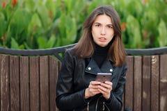 Portrait émotif d'une femme assez frustrante de brune de jeunes reposant dehors le parc de ville portant le manteau en cuir noir  photographie stock libre de droits