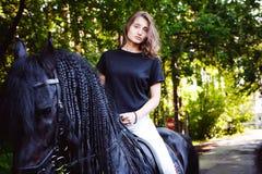Portrait émotif d'une femme de cavalier d'amazone, animal familier frison noir de pur sang d'étalon Photographie stock libre de droits
