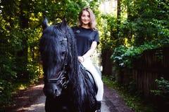 Portrait émotif d'une femme de cavalier d'amazone, animal familier frison noir de pur sang d'étalon Image libre de droits