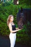 Portrait émotif d'une femme de cavalier d'amazone, animal familier frison noir de pur sang d'étalon Photo stock