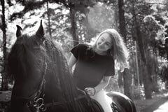 Portrait émotif d'une femme de cavalier d'amazone, animal familier frison noir de pur sang d'étalon Photos stock