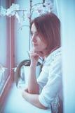 Portrait étroit de femme, regardant par une fenêtre à la maison photographie stock libre de droits