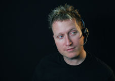 Portrait. Of handsome guy isolated in black with headphones and microphone having chat Royalty Free Stock Photos