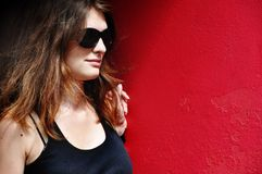 Portrait. Girl with brown hair near red wall Royalty Free Stock Image