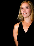 Portrait. Blond woman in a black dress on a black background.  Smiling Stock Photo