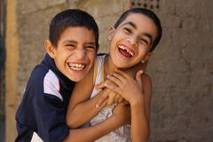 Portrait of 2 boys playing and laughing, street background in giza, egypt. Portrait of 2 boys playing, street background in Giza, Happy kids playing in the Stock Photo