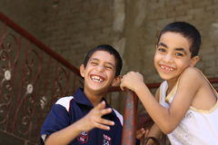 Portrait of 2 boys playing and laughing, street background in giza, egypt Stock Photos