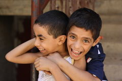 Portrait of 2 boys playing and laughing, street background in giza, egypt. Portrait of 2 boys playing, street background in Giza, Happy kids playing in the Royalty Free Stock Photos