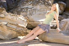 Portrait. Blond girl in green on sandstone background Royalty Free Stock Images