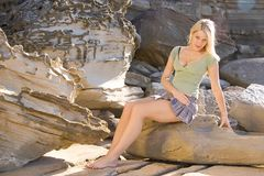 Portrait. Blond girl in green on sandstone background Royalty Free Stock Photo