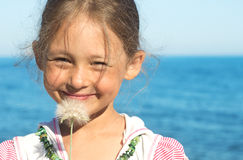 Portrait. Of a little girl with the dandelion on the background of the sea close-up Royalty Free Stock Photos