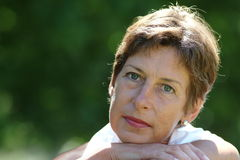 Portrait. Middle aged woman sitting in a park Royalty Free Stock Photo