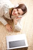 Above of smiling young woman with headphones and laptop. Portrait from above of smiling young woman with headphones and laptop Royalty Free Stock Photos