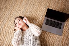 Above of smiling young woman lying down with laptop and headphones. Portrait from above of smiling young woman lying down with laptop and headphones Stock Image