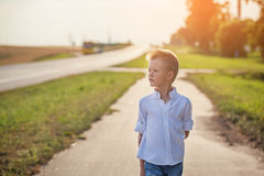 Portrait of achild on the road in the sunny day Royalty Free Stock Photography