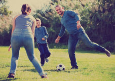 Portrait of active family playing soccer. Portrait of active cheerful family playing soccer with son outdoors royalty free stock photo