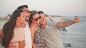 Portrait of Active Four People Taking Selfie Using Smartphone on the Beach at Summer Vacation Spending Time Together. During Windy Weather and Enjoying the stock video