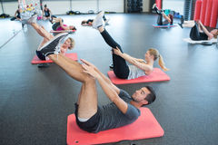 Portrait active people doing leg stretching on exercise mat Stock Photos