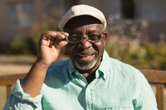 Senior man in spectacle smiling in the park. Portrait of active senior African-American man in spectacle smiling in the park royalty free stock photo