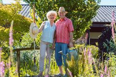 Portrait of an active senior couple holding gardening tools in the garden stock images