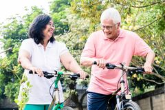Portrait of active senior couple standing on bicycles. Portrait of active senior couple smiling while standing on bicycles outdoors in summer Stock Photo
