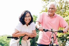 Portrait of active senior couple standing on bicycles. Portrait of active senior couple smiling while standing on bicycles outdoors in summer Stock Image