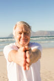 Portrait of active senior man practicing yoga at beach. On sunny day Stock Images