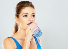 Portrait of active woman drinking mineral water of bottle. Studio portrait Stock Photography