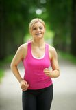 Portrait of an active young woman jogging in the park Royalty Free Stock Images